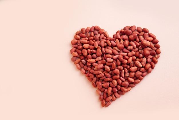 Арахис выложен в форме сердца сырой арахис на розовом пастельном фоне.