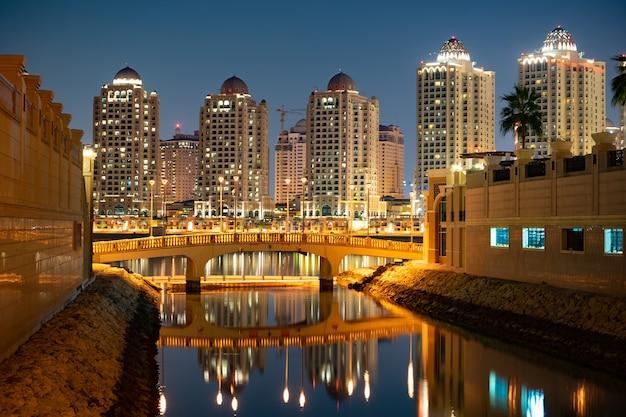 Жемчужно-катарские здания с мостом и водой в дохе, катар.