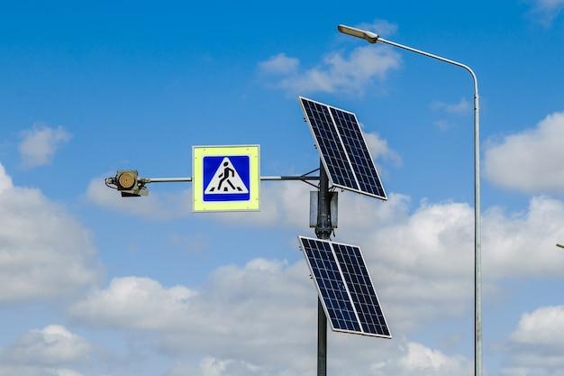 Знак пешеходного перехода с питанием от солнечных батарей, установленный над дорожными знаками и правилами