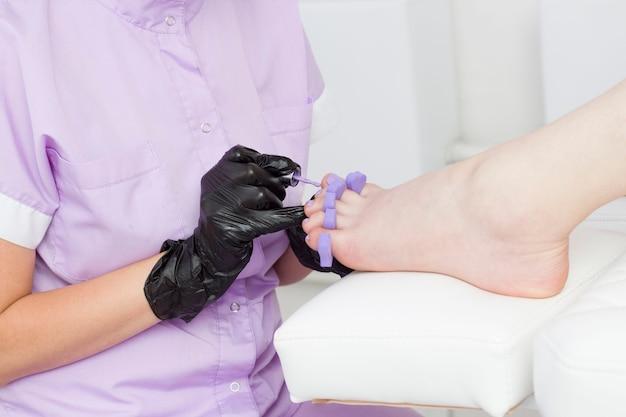 Мастер педикюра наносит лак лилового, пурпурного цвета.