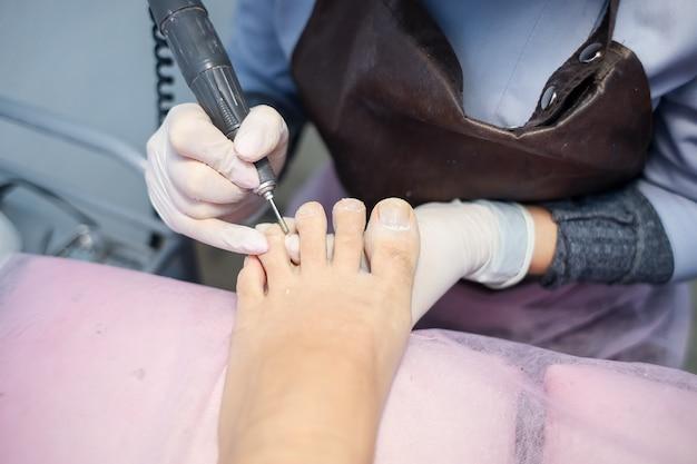 Мастер педикюра подготавливает кутикулу ногтей на ногах клиента.
