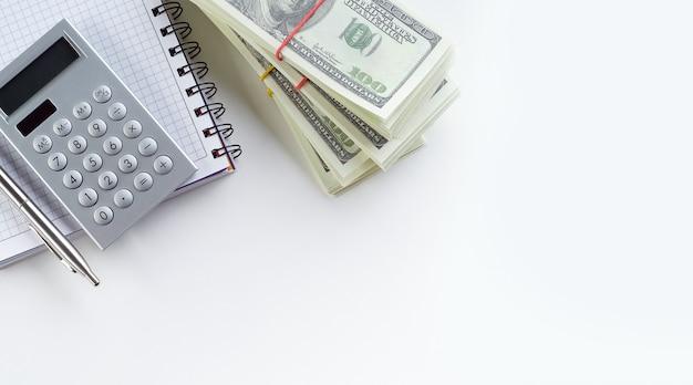 ペンと電卓は、開いているノートブックまたはメモ帳にあります。その隣にはアメリカドル紙幣の山があります。財務会計、贈収賄、汚職の概念。