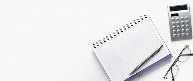 Ручка лежит на открытом блокноте. рядом с очками и калькулятором.