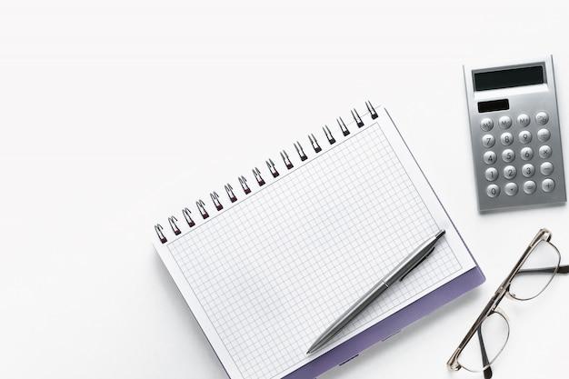 Ручка на открытом блокноте. рядом с очками и калькулятором. чистый лист блокнота с деталями бизнесмена или бухгалтера. концепция финансовой отчетности.