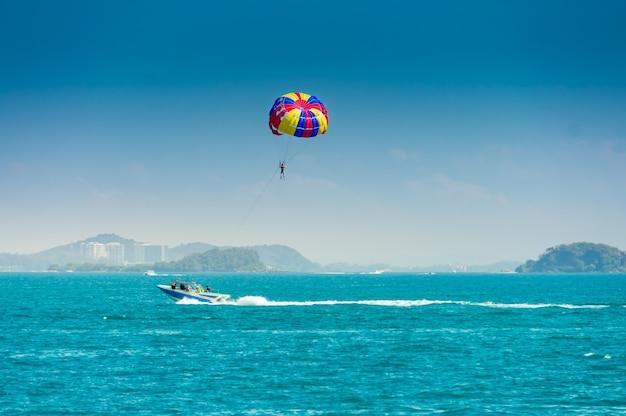 사람들은 태국에서 바다에서 낙하산을 연주합니다.