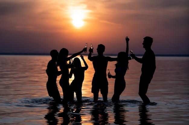 석양을 배경으로 저녁 해변 파티에서 춤추는 사람들