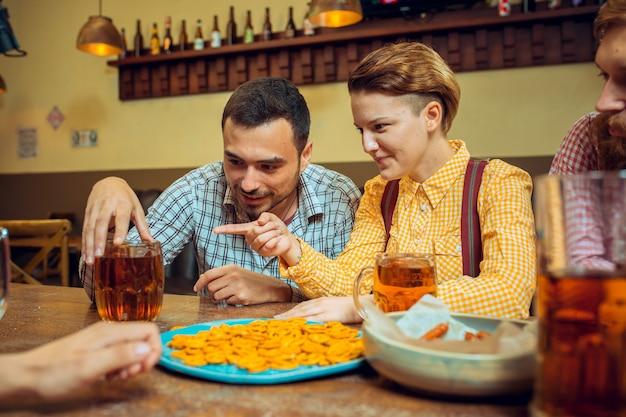 Концепция людей, досуга, дружбы и общения - счастливые друзья пьют пиво, разговаривают и звонят бокалами в баре или пабе