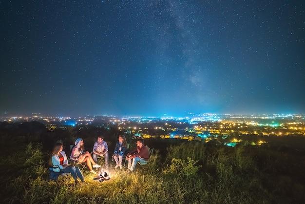 Люди отдыхают у костра на фоне звездного неба. вечер ночное время
