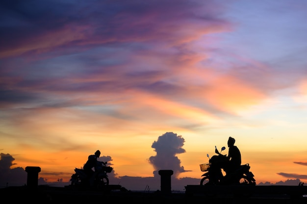 夕焼け空と海で人々のシルエット
