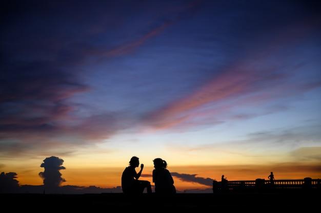 Силуэт людей на море с закатным небом