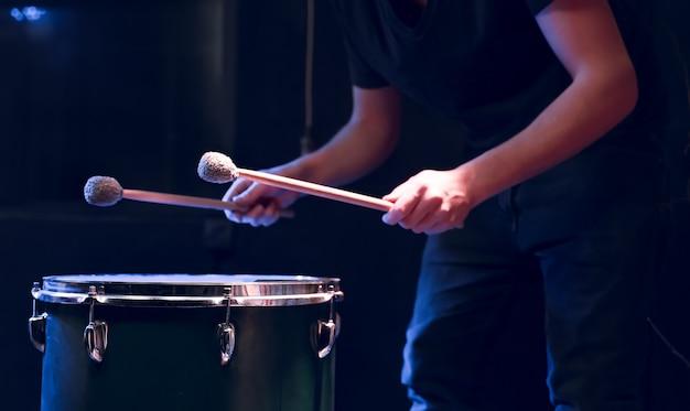 타악기 연주자는 아름다운 조명이있는 어두운 방에서 바닥에 막대기로 연주합니다. 콘서트 및 성능 개념.