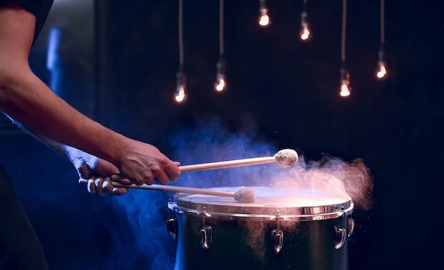 타악기 연주자는 스튜디오 조명 아래에서 바닥 톰에 막대기로 연주합니다. 콘서트 및 성능 개념.