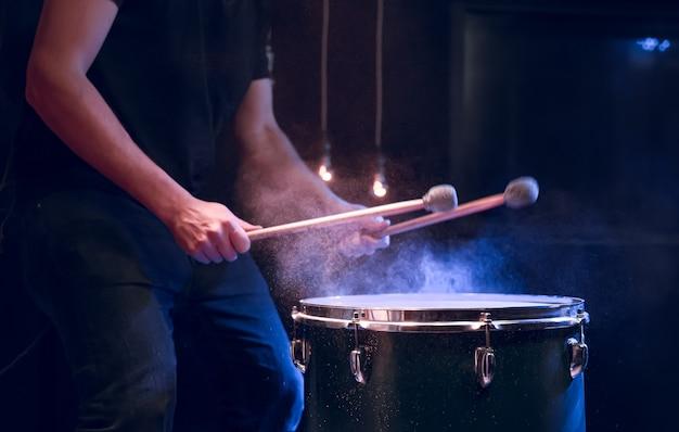 Перкуссионист играет палками на напольном томе при студийном освещении. концерт и концепция выступления.