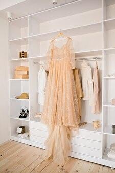 ハンガーにフルスカートの完璧なウェディングドレス。式典の前に、肩にベージュのウェディングドレス