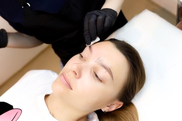 영구 메이크업 아티스트는 문신 절차 후 고객의 눈 주위 피부를 치료합니다.