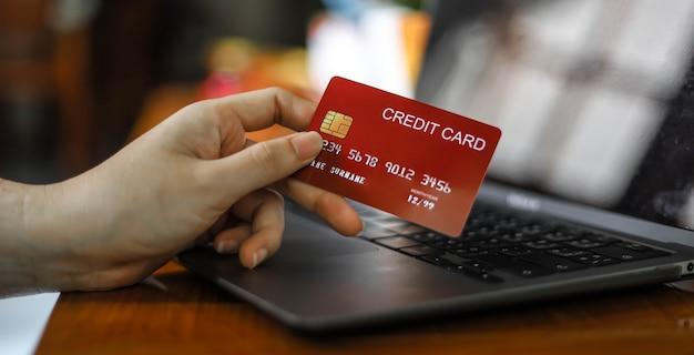 その人はクレジットカードを持っており、オンラインで商品の支払いをするためにクレジットカード情報を入力しています。クレジットカードは店頭とオンラインショッピングの両方で商品とサービスの支払いを行うことができます。