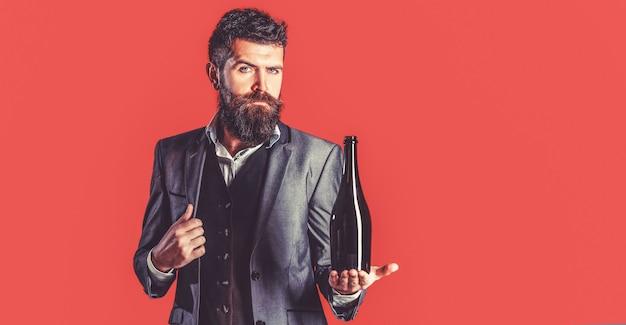 Человек держит в руке бутылку красного вина. мужчина держит бутылку с шампанским, вином. бородатый мужчина с бутылкой шампанского и бокалом.