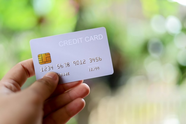 У человека есть кредитная карта, с помощью которой можно оплачивать товары и услуги в розничных магазинах, ресторанах или совершать покупки в интернете. концепция использования кредитной карты.