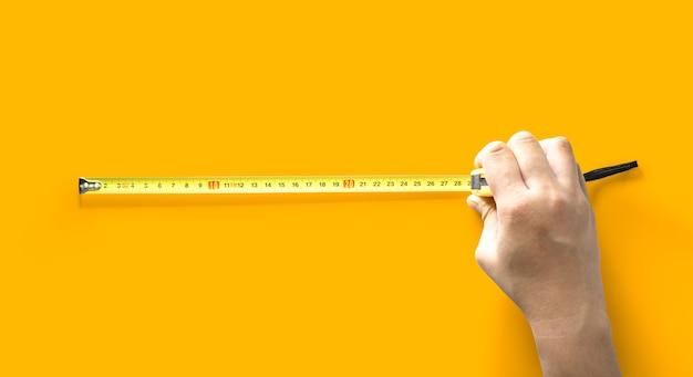 그 사람은 길이 측정기, 길이 측정 도구, 노란색 배경 및 클리핑 패스에 격리됨을 사용하고 있습니다.