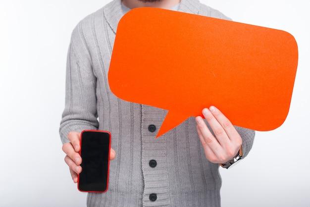 電話はあなたに言うべき何かを持っています!スマートフォンとオレンジ色のスピーチを握っている男。