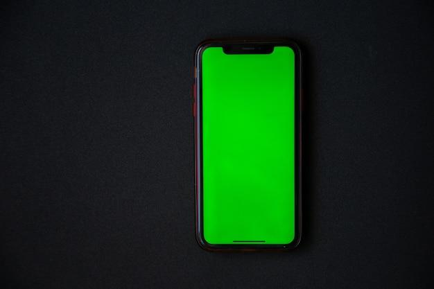 緑色の画面の電話は黒い背景の高品質の写真にあります