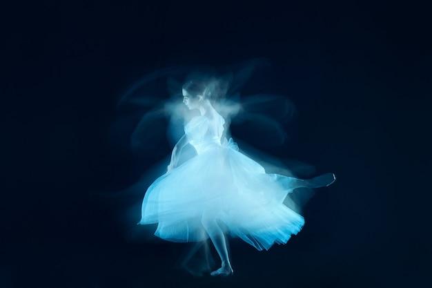 アートとしての写真-暗い背景のベールを通して美しいバレリーナの官能的で感情的なダンス。 1つのモデルのストロボ画像