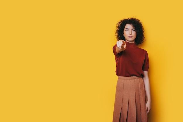 Фотография шикарной дамы с кудрявыми волосами и потрясающей улыбкой указывает на камеру и что-то рекламирует.