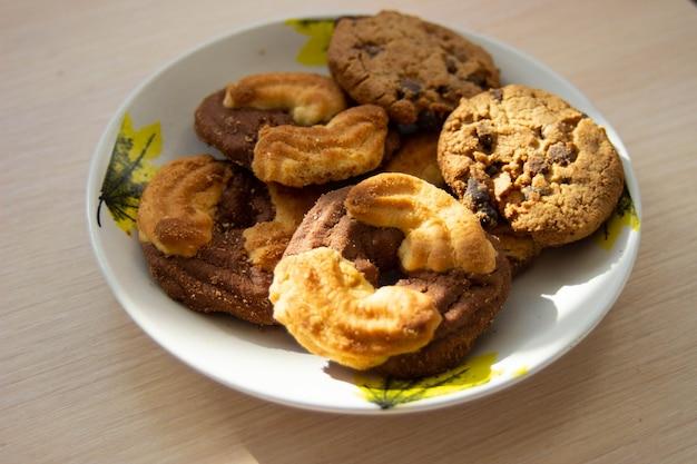 プレート上のチョコレートチップクッキーとショートケーキビスケットの山の写真