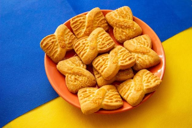 プレート上のクッキーまたはショートケーキビスケットの山の写真。全国クッキーデーの背景。ウクライナの旗。朝ごはん。