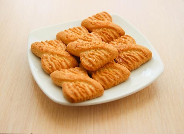 プレート上のクッキーまたはショートケーキビスケットの山の写真。全国クッキーデーの背景