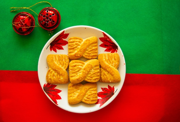 赤い鐘が付いている皿の上のクッキーまたはショートケーキビスケットの山の写真。全国クッキーデーの背景。サンタさんのクリスマスの朝食。