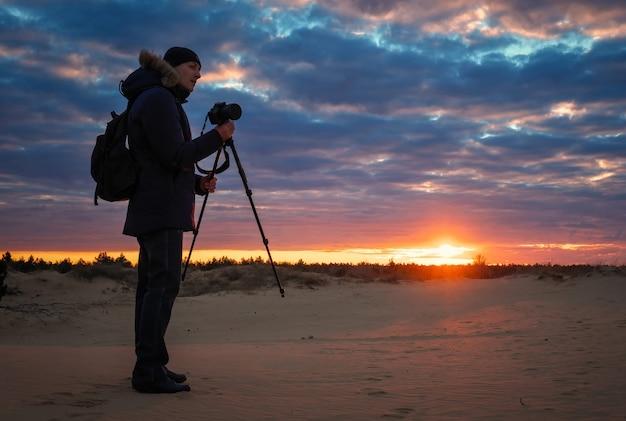 写真家は、日没時に砂の上で風景を撮影します。美しいカラフルな日の出の空。創造性と成功。