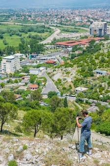 写真家は夏の日に街のパノラマの写真を撮ります。