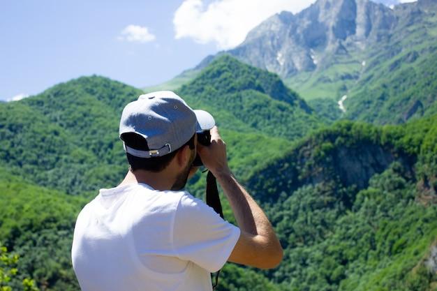 青空の下、山と森をカメラマンが撮影