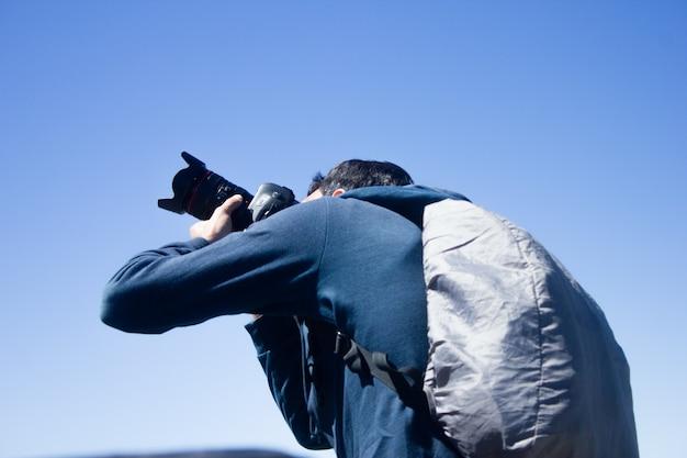 カメラマンはバックパックを背負って青空の下で写真を撮る
