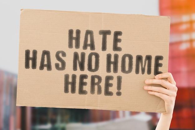 Фраза «ненависти здесь нет дома!» на баннере в мужской руке с размытым фоном. равенство. права человека. мир. мирный. свобода. отношение. справедливость