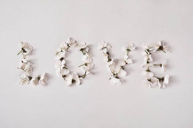 하얀 작은 벚꽃으로 만든 사랑이라는 문구 또는 단어. 기념일 또는 축제 이벤트에 대한 엽서 또는 초대장에 대한 최소한의 개념.