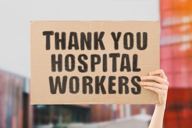 手元にあるプラカードに「ありがとう病院の労働者」というフレーズ。人間は碑文と段ボールを保持しています。医療スタッフへの感謝。ヒーロー。命を救う人々。感謝。生活