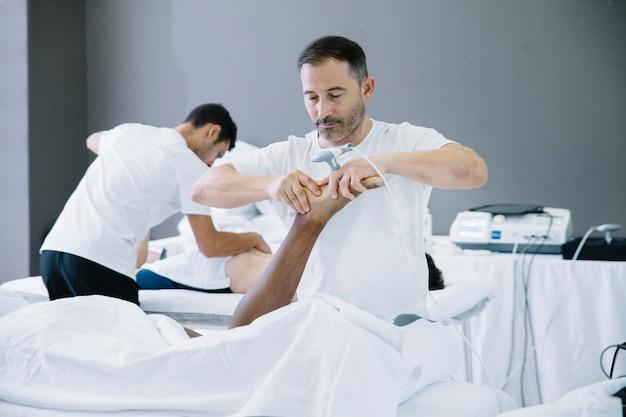 Физиотерапевт лечит мужчину