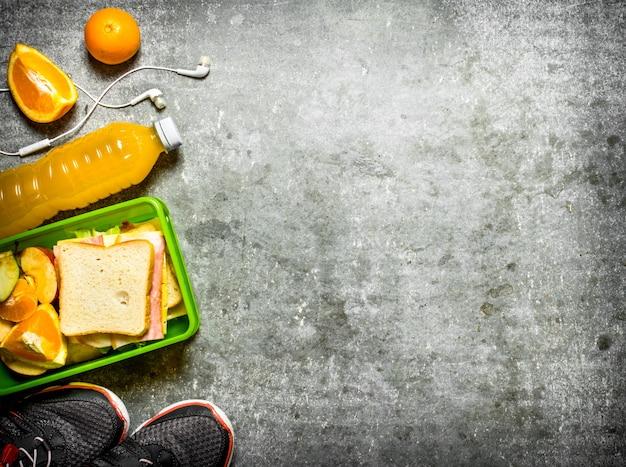 石のテーブルにサンドイッチ、オレンジジュース、フルーツをセットしたピクニック