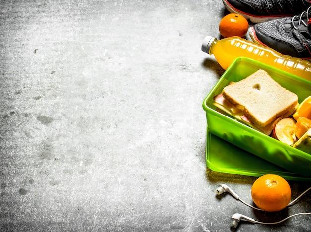 ピクニックセット。サンドイッチ、オレンジジュース、フルーツ。石のテーブルの上