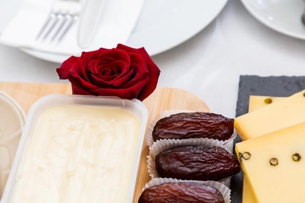 石のトレイと木製のトレイにある美しい朝食用テーブル、バラ、チーズ、バター、イチゴの写真