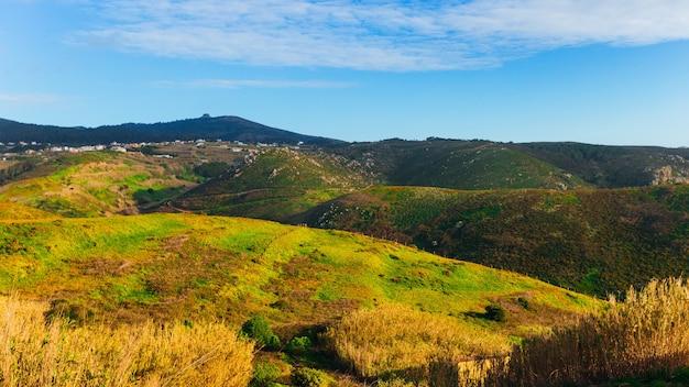Живописные горы покрыты горной растительностью и небольшой поселок.