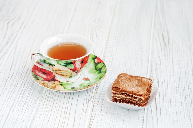 Кусок шоколадного торта и чашка чая.