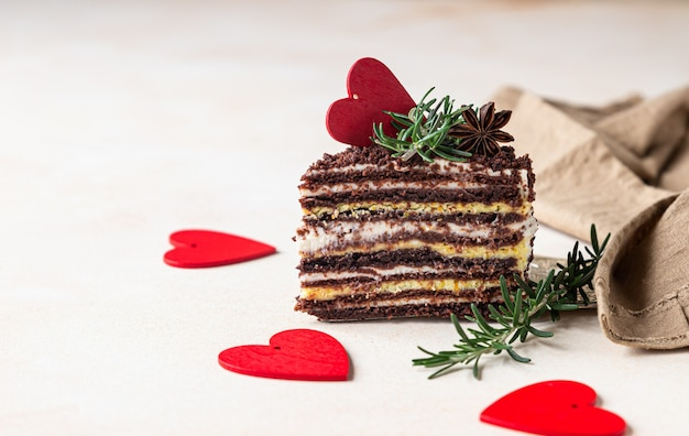 Кусок шоколадного слоеного торта и красных сердечек