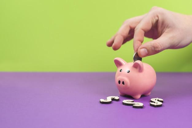 貯金箱は紫と緑のテーブルにピンクです