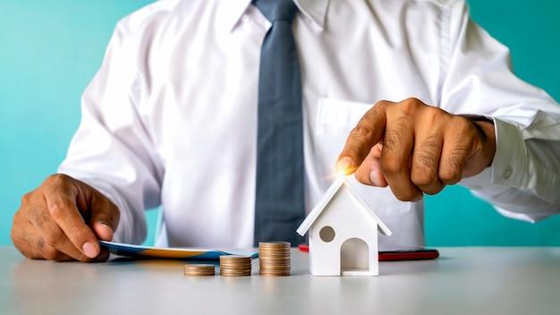 동전 더미가 올라가고 투자자들의 손이 대출, 금융, 모기지, 부동산 아이디어를 시뮬레이션하는 집을 가리키고 있습니다.