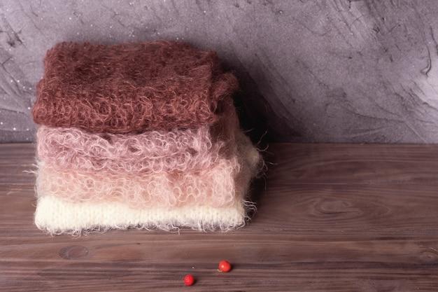Куча пастельных шерстяных шарфов на деревянном фоне