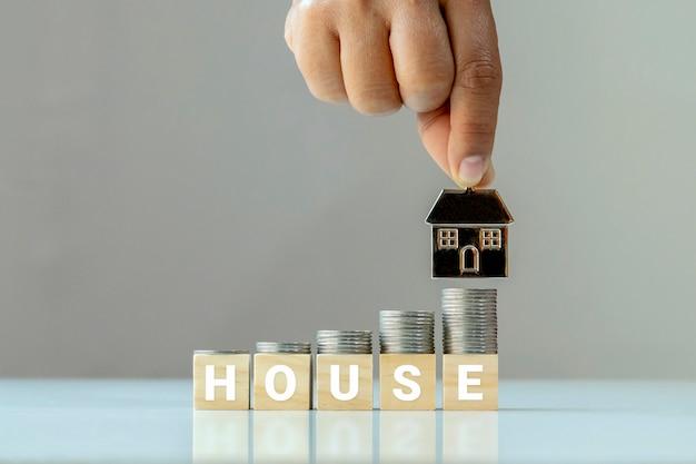 동전 더미는 집이라는 단어와 집 모델을 들고있는 손으로 나무 큐브에 놓입니다. 부동산 회사에 대한 금융 및 투자 아이디어.