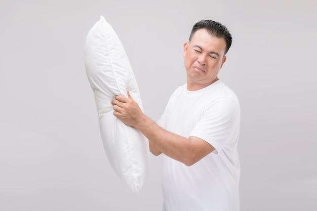 枕は悪臭がします。白い枕を持って悪臭を放つ肖像画アジア人男性。